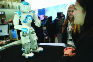 HANOVER, GERMANY - MARCH 14: A stand hostess talks to a NAO Watson robot at the IBM stand at the 2016 CeBIT digital technology trade fair on the fair's opening day on March 14, 2016 in Hanover, Germany. The 2016 CeBIT will run from March 14-18. (Photo by Sean Gallup/Getty Images)