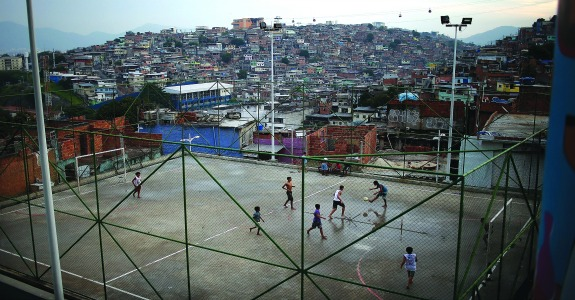 RIO DE JANEIRO, BRAZIL - MAY 18: Kids play soccer in the Complexo do Alemao pacified community, or 'favela' on May 18, 2014 in Rio de Janeiro, Brazil. Ahead of the 2014 FIFA World Cup, Rio has seen an uptick in violence in its pacified slums, including Complexo do Alemao. A total of around 1.6 million Rio residents live in shantytowns, many of which are controlled by drug traffickers. (Photo by Mario Tama/Getty Images)